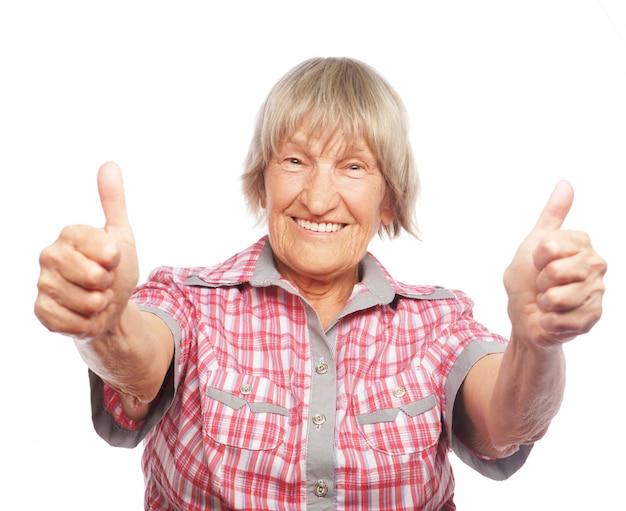 Старая женщина показывает знак ок на белом