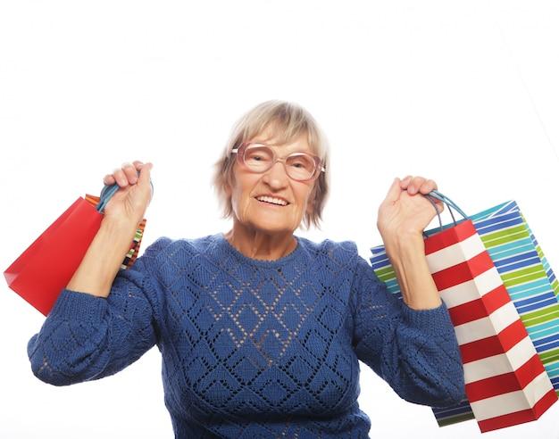 Счастливая старшая женщина с хозяйственными сумками