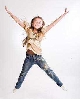 小さな女の子が白い背景を飛び越える
