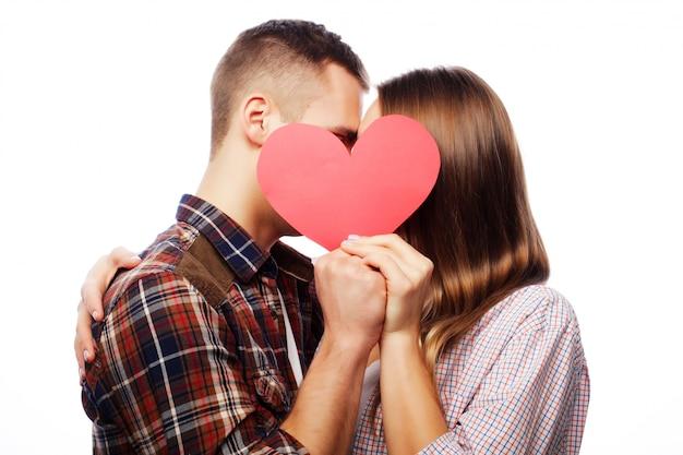 赤いハートを保持している愛の幸せなカップル。