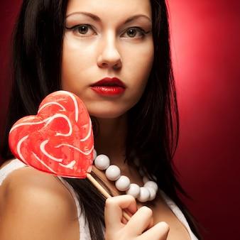 Довольно молодая женщина, держащая лолли поп.