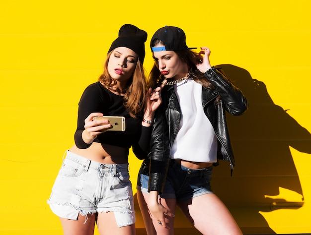Девочки-подростки на открытом воздухе делают селфи на телефоне.