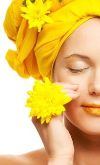 黄色の菊を持つ若い女性