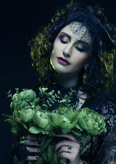 大きな緑の花を保持しているブリクト顔を持つ女性
