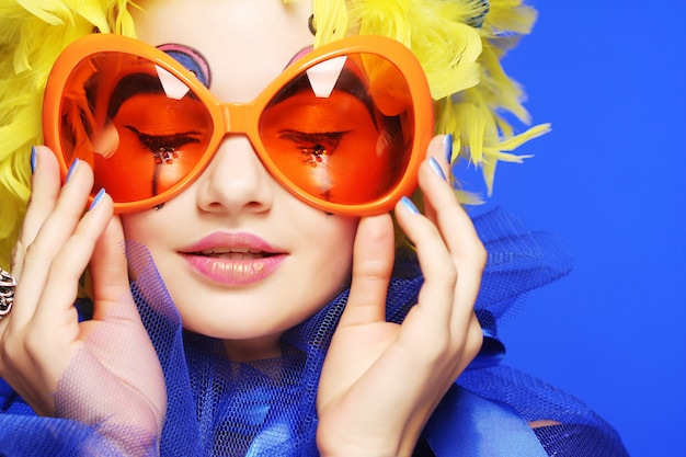 黄色い髪とカーニバルメガネの女性