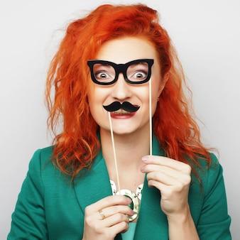 口ひげとメガネを保持している若い女性