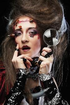 Женщина с творческим макияж, держа увеличительное стекло