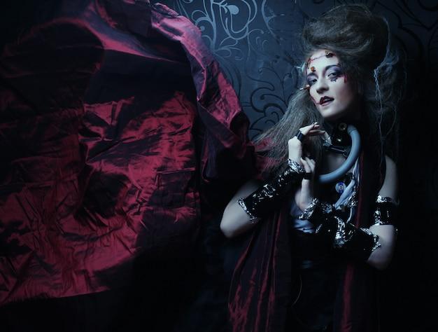 Молодая женщина с креативным макияжем в красном плаще