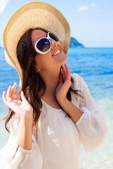 Счастливая женщина в шляпе на пляже