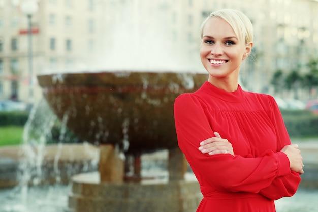 赤いドレスを着ているファッショナブルな若いブロンドの女性