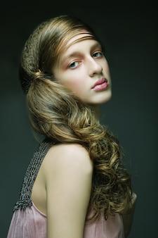 Красивая женщина с длинными светлыми вьющимися волосами.