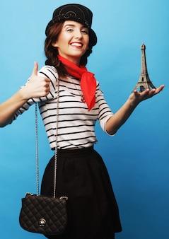 小さな金属エッフェル塔を保持している若い女性