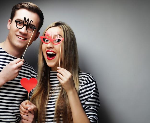棒でパーティーメガネと帽子を保持しているカップル