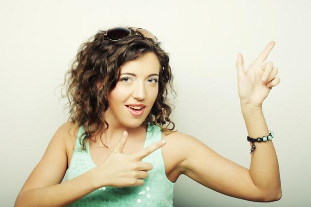 Красивая молодая женщина показывает палец вверх жест