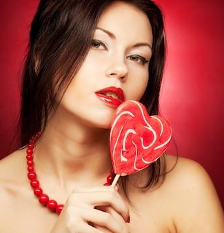 キャンディーポップを保持しているかなり若い女性。