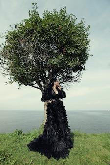 Женщина позирует на берегу моря. темная королева