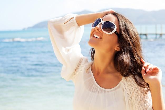 Счастливая женщина в белом платье летом на пляже.