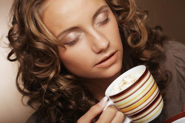 Молодая девушка пьет чай или кофе