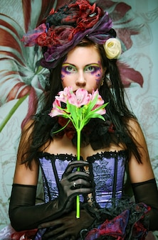 Женщина с творческим макияжем в стиле куклы с цветком
