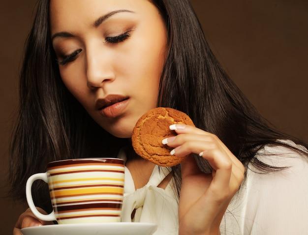 Азиатская женщина с кофе и печенье.
