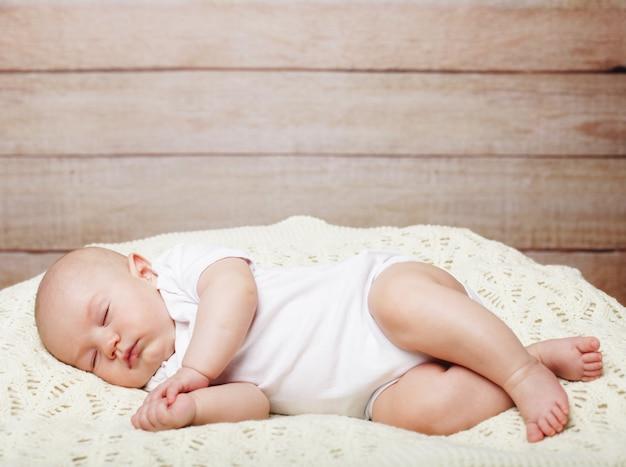 寝ている間にベッドに横になっている赤ちゃん