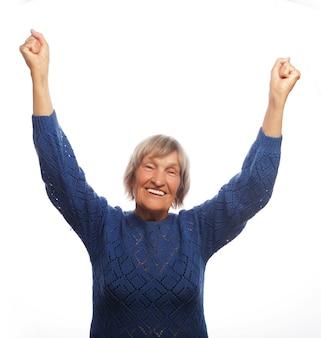 Старшая женщина показывать победу над белой предпосылкой