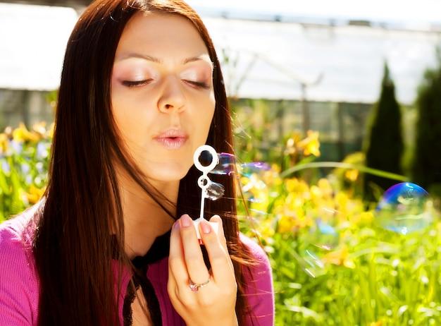 背景の草に対する少女吹くシャボン玉