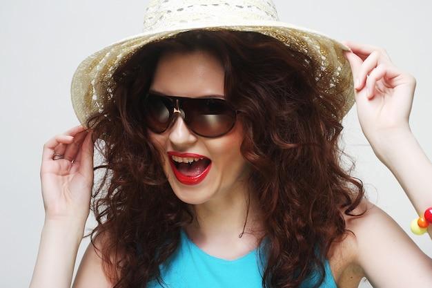 帽子とサングラスを着ている若い驚く女性