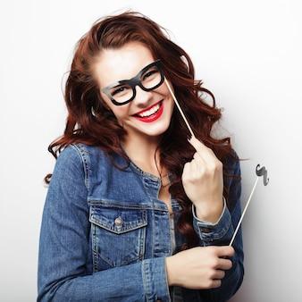 Партийный имидж. игривая молодая женщина, держащая партийные очки.