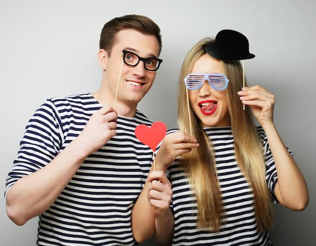 Пара, держащая партийные очки и шляпу на палках