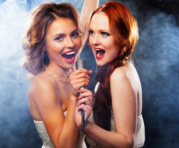 Красавицы девушки с микрофоном поют и танцуют