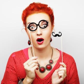 スティックに口ひげとメガネを保持している女性。