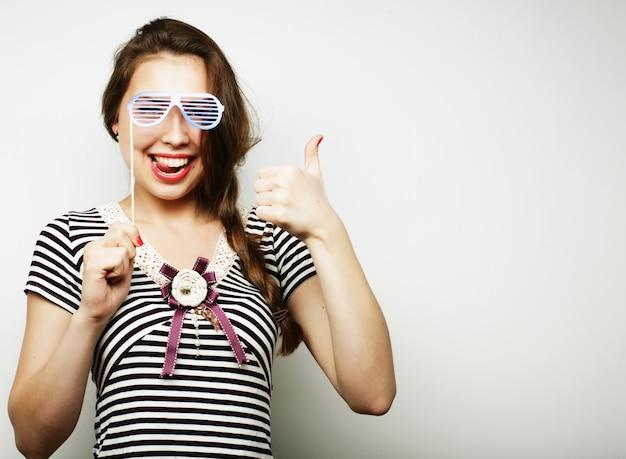 パーティーグラスを保持している遊び心のある若い女性。