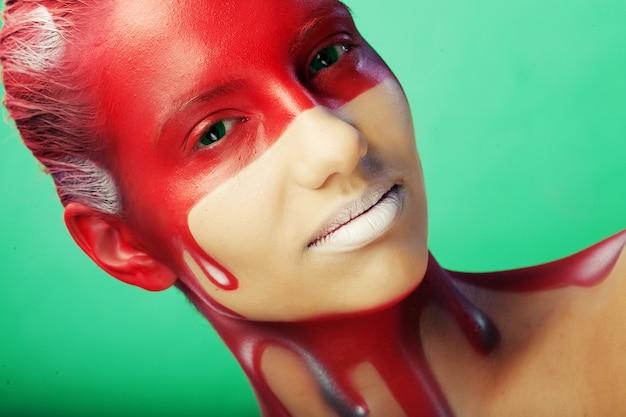 創造的な顔アートを持つ若い女性