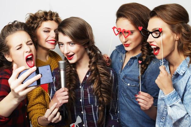 Красивые стильные хипстерские девушки поют караоке