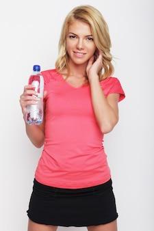 水のボトルとスポーティな女性