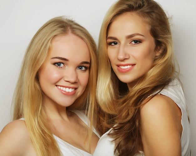 Две молодые подруги, стоя вместе и с удовольствием.