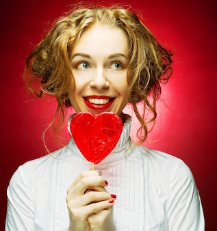 赤い背景の上の心キャラメルを持つ女性