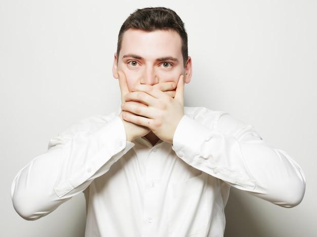 Шокирован молодой человек, охватывающий рот руками