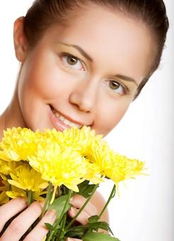 黄色の菊を持つ若い女性の画像
