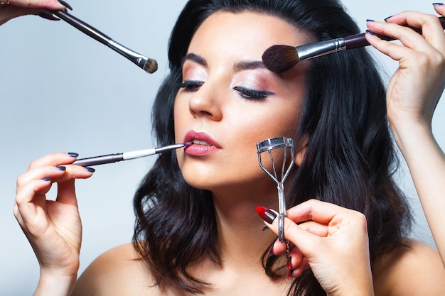 Крупным планом лицо молодой женщины со всеми видами инструментов для макияжа