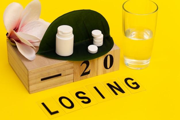 Стакан воды и таблетки для похудения