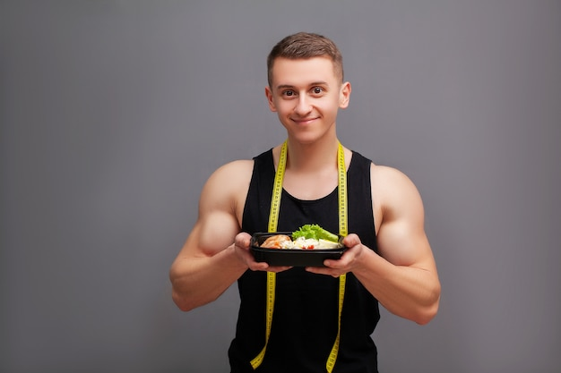 Мужчина держит коробку, полную белков богатых продуктов для спортивного питания