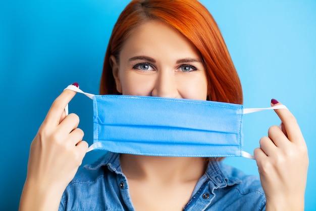 青の背景にウイルスから保護するために口と鼻を覆うマスクを保持している女性。