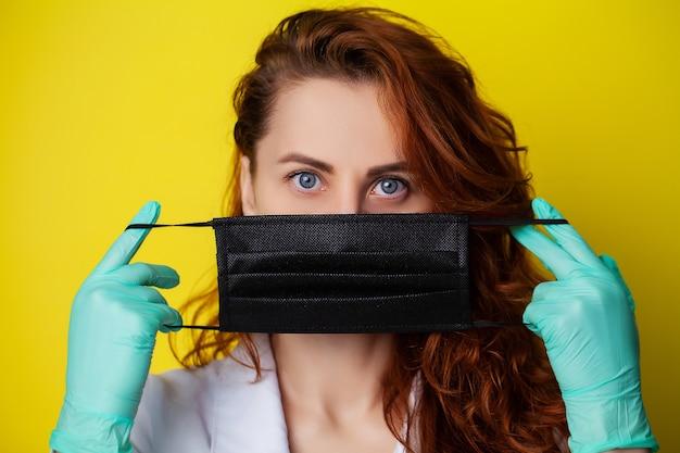 ウイルスから保護するために口と鼻を覆うマスクを保持している女性