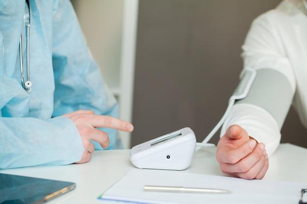 Врач измеряет давление пациента в клинике