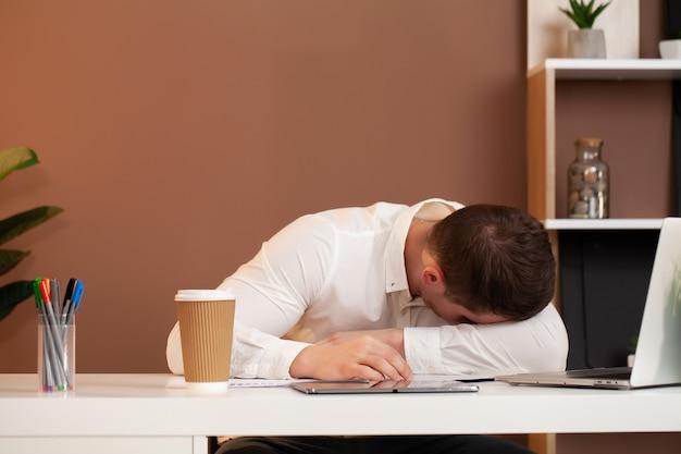 Утомленный работник работая на столе на офисе компании