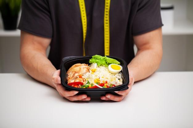 Макрофотография человека, держащего коробку с белковой пищей для спортивного питания