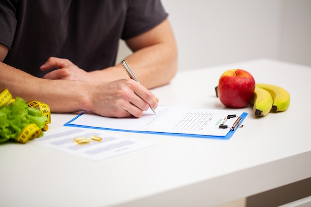 トレーナーはトレーニングプログラムと健康的な食事計画を作成します