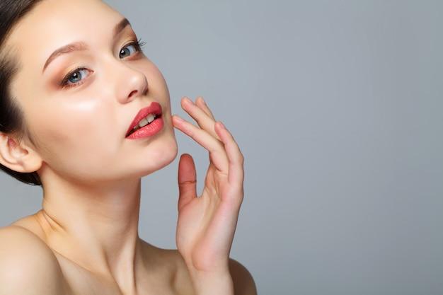 顔に化粧品クリームを持つ女性の美しさの顔